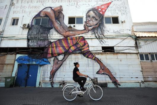 A woman rides her bicycle in Old Jaffa Port, Tel Aviv, Israel.